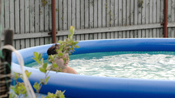 Boy swimming in inflatable pool in the yard Footage