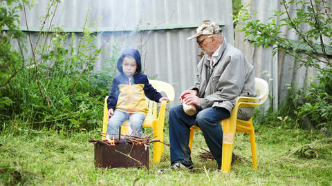 Grandfather and his grandson sitting by the fire o Footage