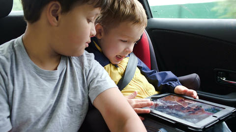 Boys with tablet computer during traveling by car Footage