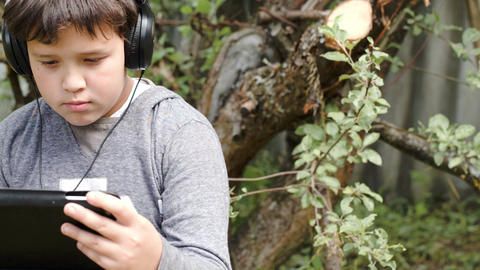 Boy in headphones with touchpad outdoor Stock Video Footage