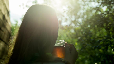 Girl drinking hot tea outdoor at sunset Stock Video Footage