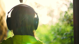 Girl listening to music in headphones outdoor GIF