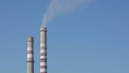 Industrial smokestacks against the blue sky Footage