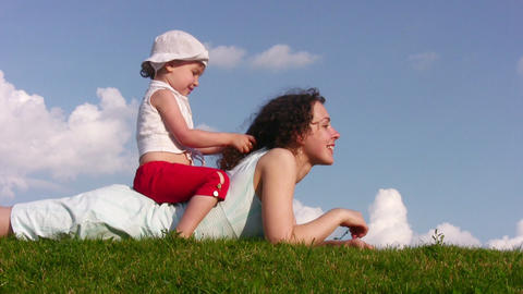 little girl on mother on meadow Stock Video Footage