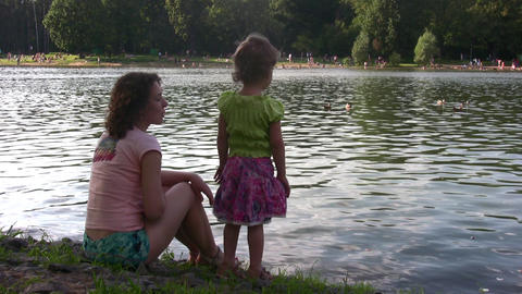 mother with girl on pond Footage