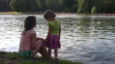 mother with girl on pond Stock Video Footage