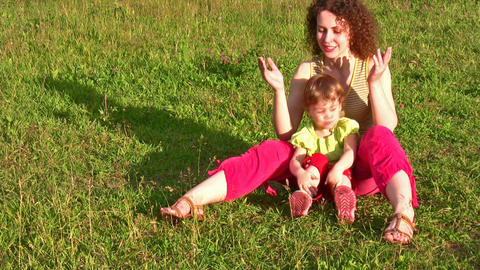 mother with little girl on grass 2 Stock Video Footage