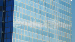 Moving clouds reflected in a glass wall of the Stock Video Footage