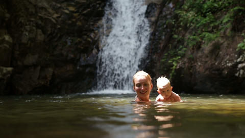 mom swimming baby waterfall Footage
