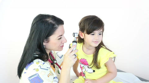 Attractive doctor examining patient's ears at the  Footage