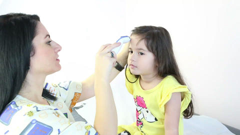 Doctor checking girl temperature Footage