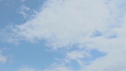 White puffy clouds move across a blue sky Time Stock Video Footage