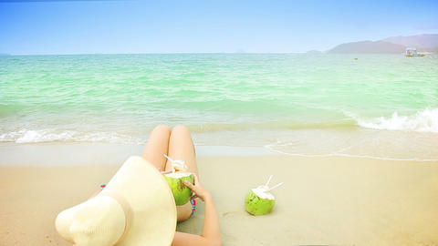 Young woman in swimsuit with coconut cocktail on t Footage