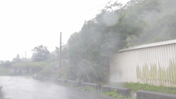 Typhoon causing strong wind and rain next to a hou Footage
