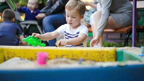 Child playing with toys in sand-pit Live Action