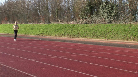 Woman running at track and field competition Stock Video Footage