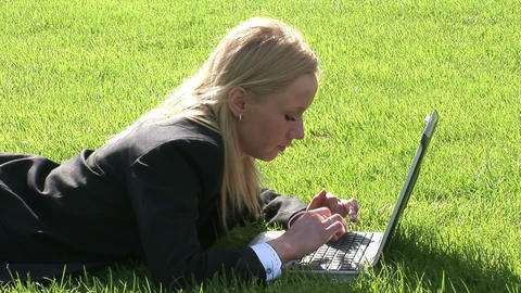 Woman lying on grass using laptop computer Footage