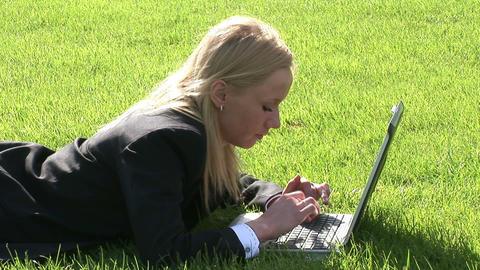 Woman lying on grass using laptop computer ビデオ