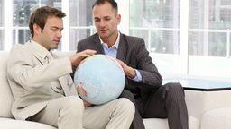 Serious businessmen looking at a terrestrial globe Stock Video Footage