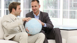 Serious businessmen looking at a terrestrial globe Footage