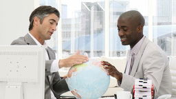 Businessmen looking at a terrestrial globe Footage