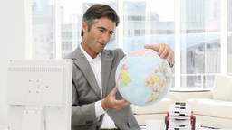 Confident businessman looking at a terrestrial glo Stock Video Footage