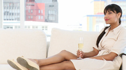 Relaxed businesswoman drinking Champagne sitting on a sofa Stock Video Footage