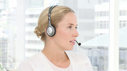 Blond business woman holding headset Footage
