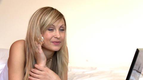 Blond woman on phone lying on bed Footage