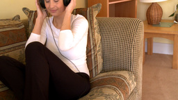 Attractive woman listening music sitting on sofa Footage