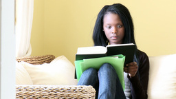 Serious woman reading a book sitting on sofa Footage