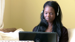 Merry woman using a laptop with headset on Footage