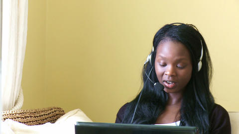 Merry young woman working at a laptop with headset Footage