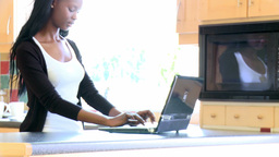 Smiling woman in the kitchen using a laptop Footage
