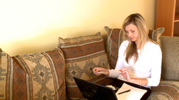Distressed woman using a laptop sitting on sofa Stock Video Footage