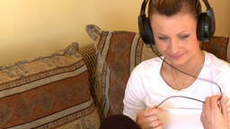 Happy woman listening music sitting on sofa Footage