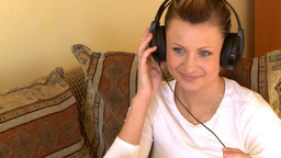 Happy woman listening music sitting on sofa Stock Video Footage
