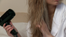 Blond woman using a blowdryer Footage