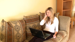 Laughing woman on phone using a laptop Footage
