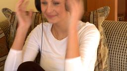 Mirthful woman listening music sitting on sofa Footage