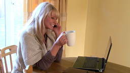Smiling woman on phone using a laptop Stock Video Footage