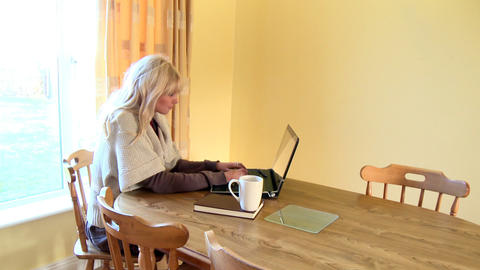 Enthusiastic woman using a laptop and drinking cof Footage