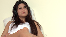 Thoughtful woman listening music lying on bed Stock Video Footage