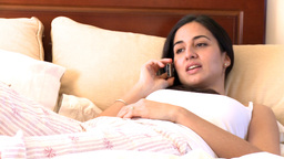 Charismatic woman talking on phone lying on bed Footage