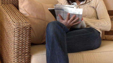 Relaxed woman reading magazine sitting on sofa Footage