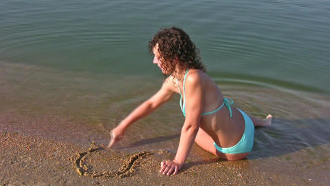 girl drawing heart on beach Stock Video Footage