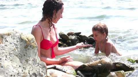 mother with girl on stone beach Stock Video Footage