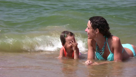 mother with little girl on splashing beach Stock Video Footage