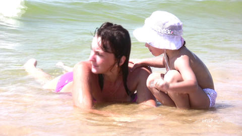 mother with little girl in hat on splashing beach Footage