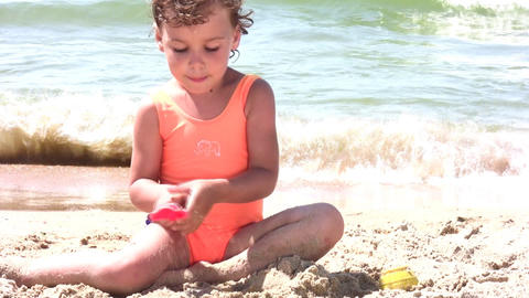 little girl play with sand on beach Footage